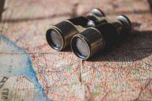 Binoculars on top of a map