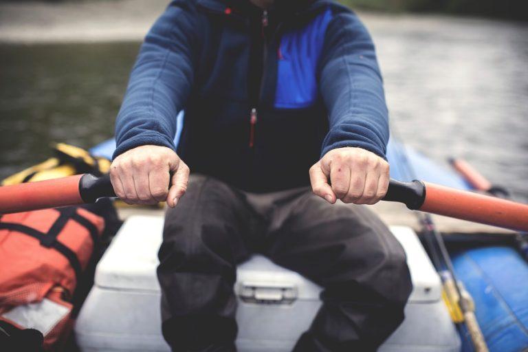 A fly angler rowing a canoe.