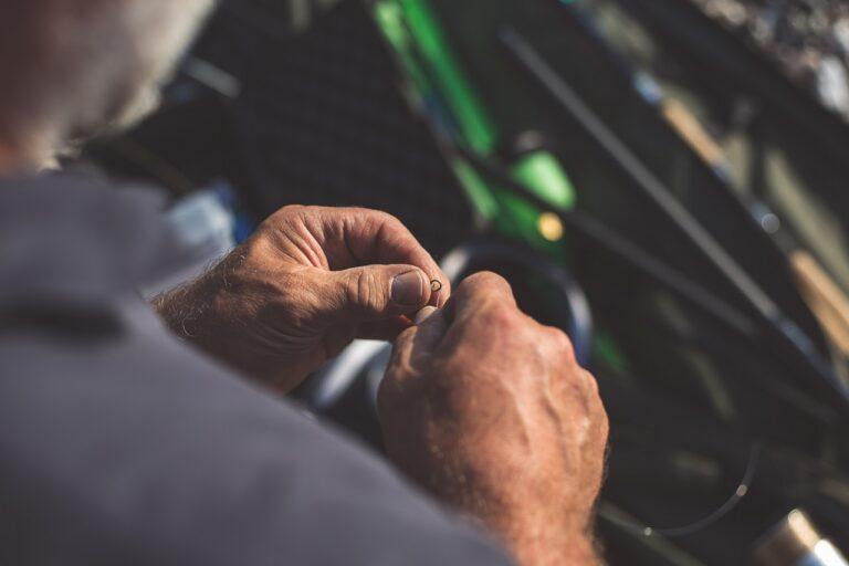 Man tying his fishing line knot.