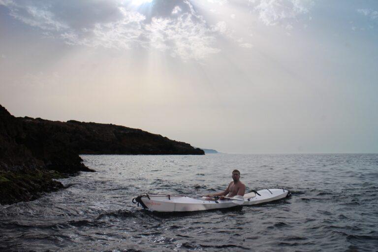 Man sitting on a foldable Kayak on water.